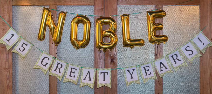 Balloons and banner spelling Noble 15 Great Years